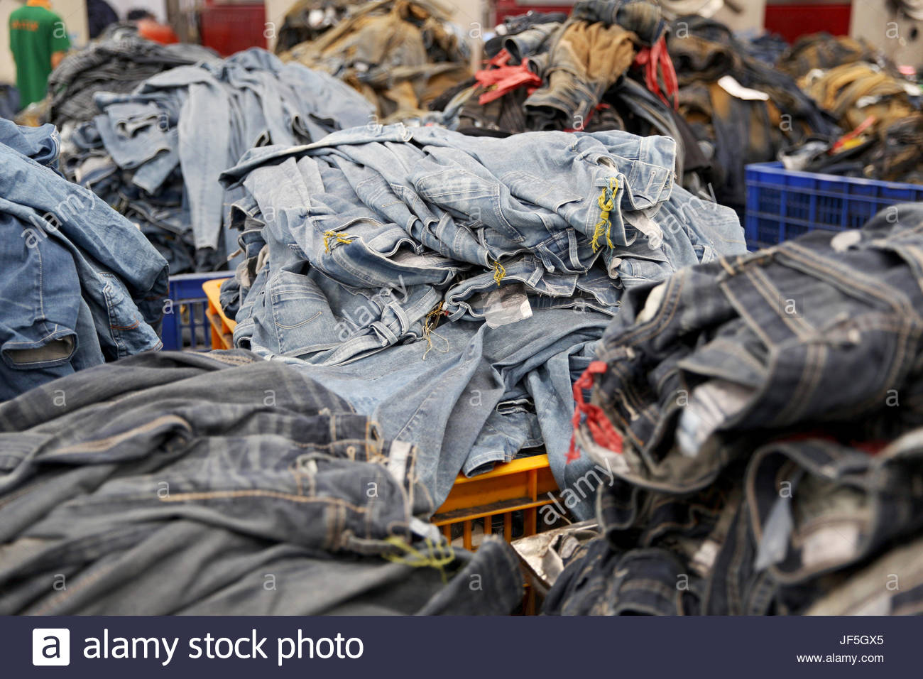 Piles of jeans at a denim factory. - Stock Image