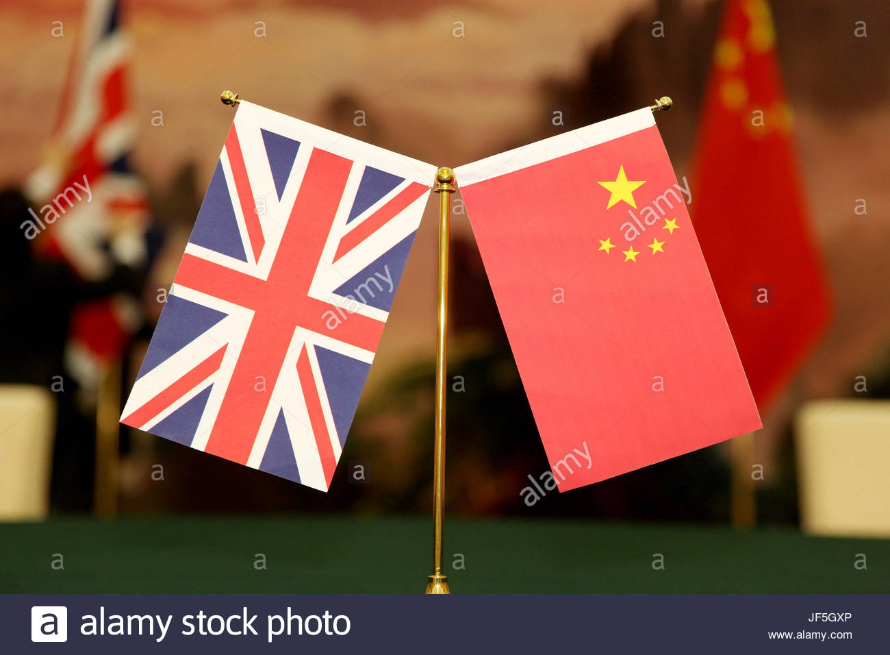 The national flags of the United Kingdom and the People's Republic of China during an official government signing - Stock Image