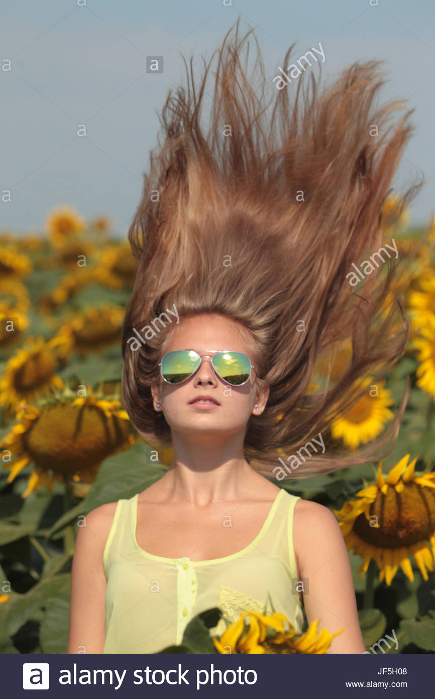 Portrait of a seventeen-year-old girl swinging her hair in a field of sunflowers, Helianthus annuus. - Stock Image
