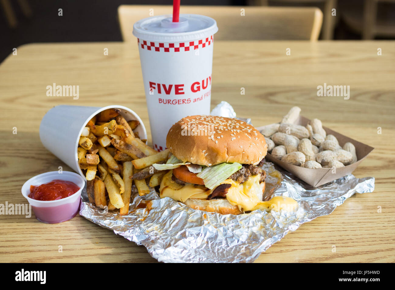 A bacon cheeseburger, French fries, and peanuts from Five Guys Burgers and Fries, an American fast casual restaurant - Stock Image