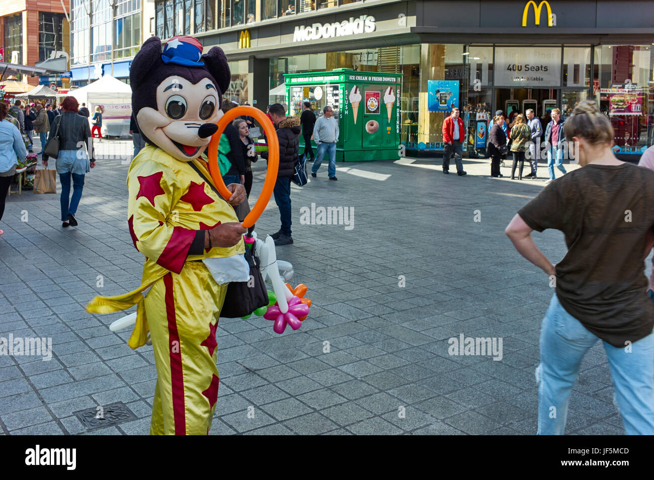 Person dressed as Mickey Mouse selling balloons in centre of Liverpool - Stock Image