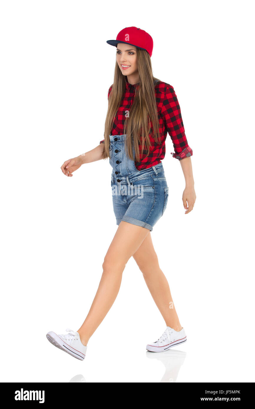 Woman in red lumberjack shirt, jeans shorts white sneakers and full cap walking and looking away. Side, front view. - Stock Image