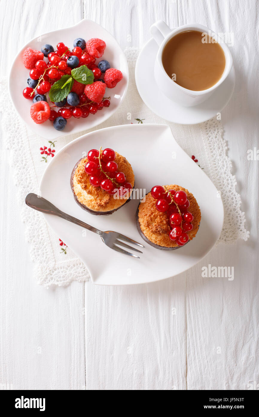 Coconut muffins with berries and coffee with milk close-up on the table. vertical view from above - Stock Image
