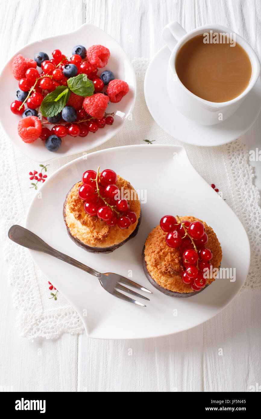 Coconut muffins with currants and coffee with milk close-up on the table. vertical view from above - Stock Image
