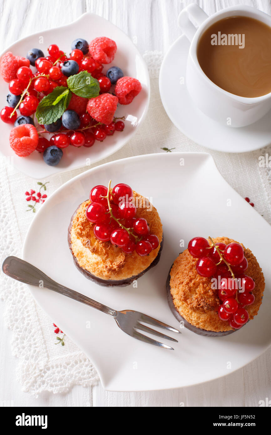 Delicious breakfast, coconut muffins, berries and coffee with milk close-up on the table. vertical view from above - Stock Image