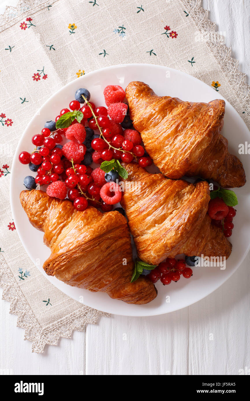 Delicious butter croissant with fresh berries close up on a plate. Vertical view from above - Stock Image