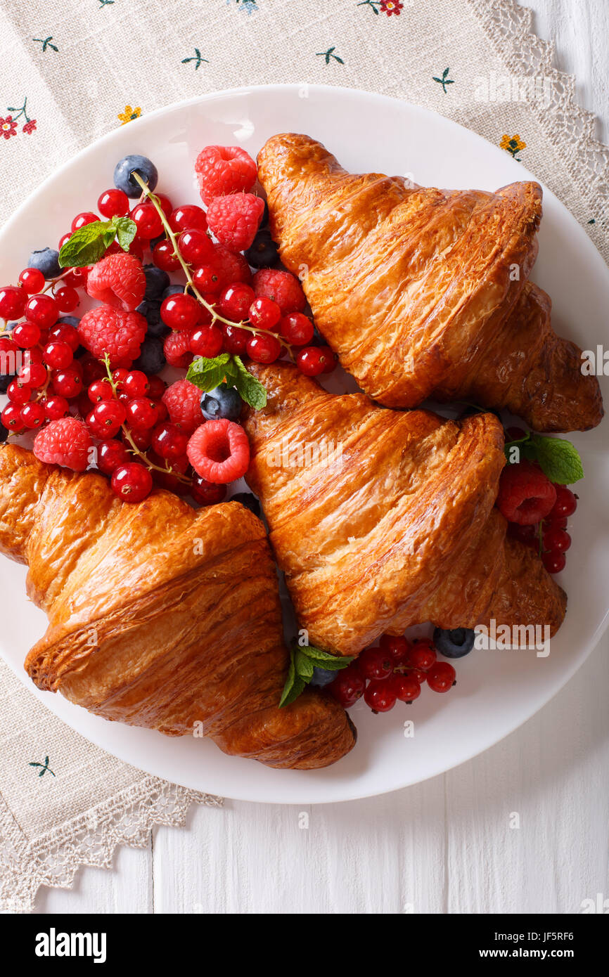 Golden croissants with fresh summer berries close-up on a plate. Vertical view from above - Stock Image