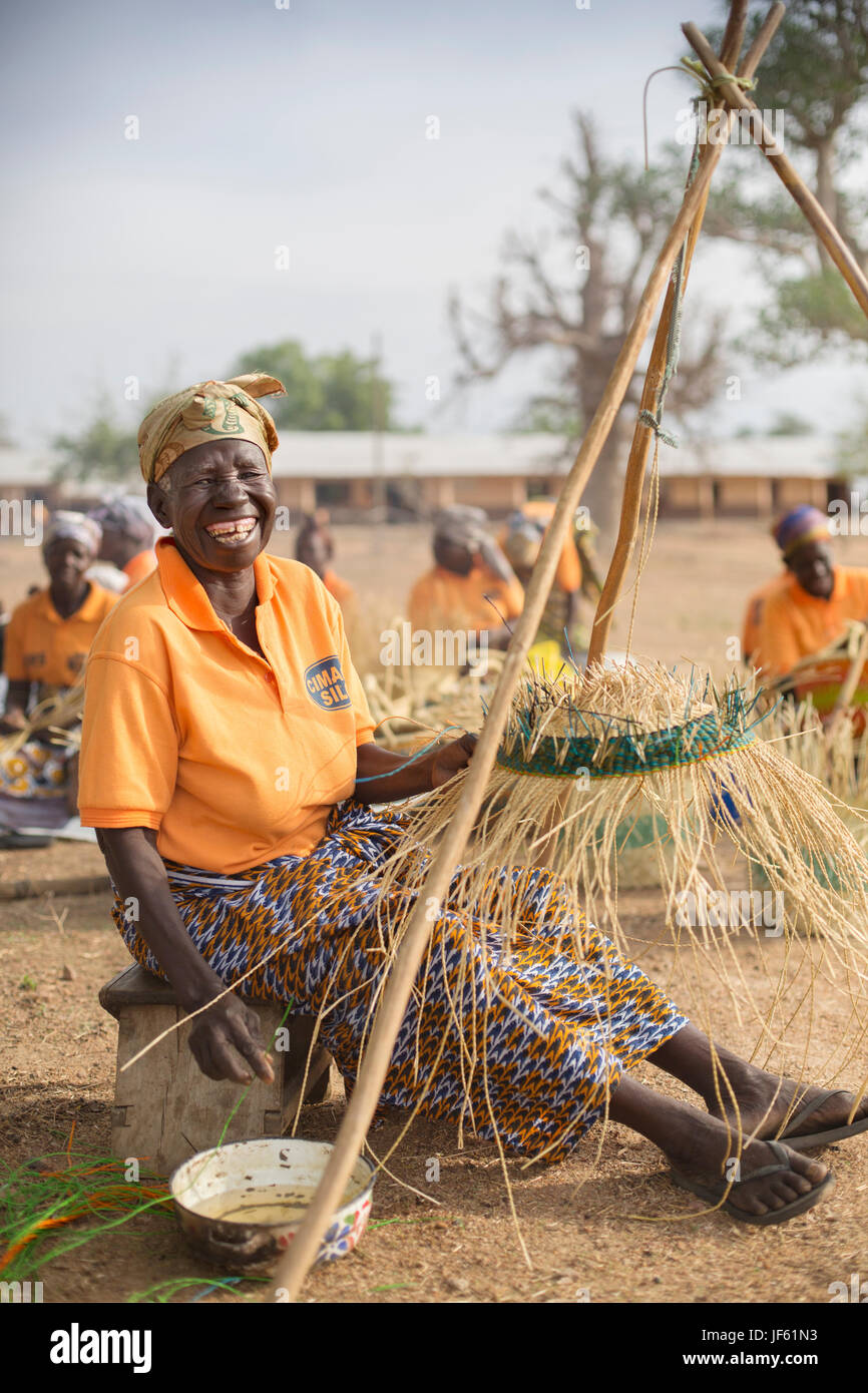 Women from a weaver's cooperative weave traditional straw baskets together in Upper East Region, Ghana. - Stock Image