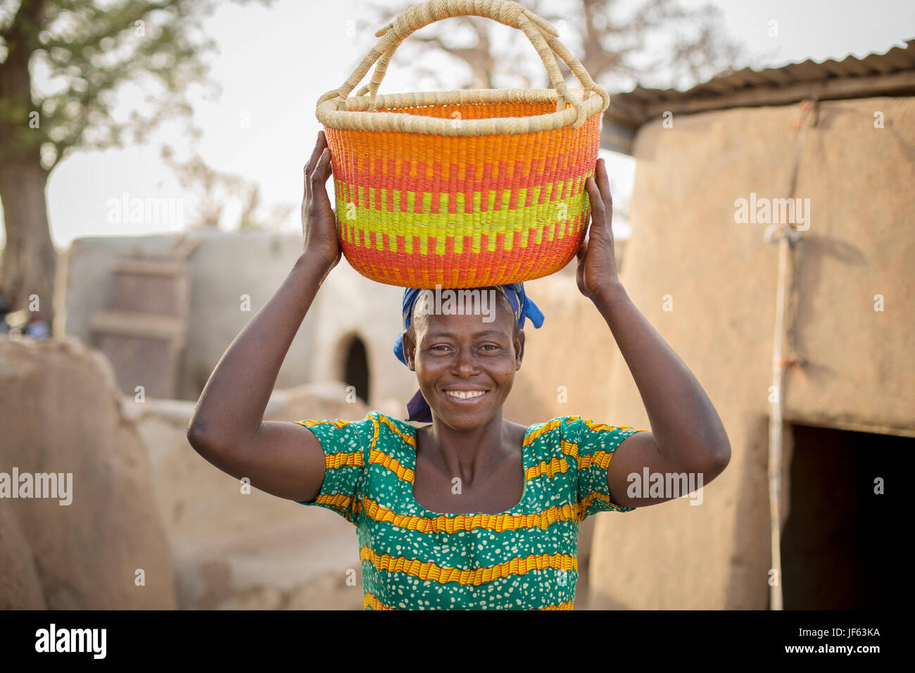 A woman holds a traditional straw basket in Upper East Region, Ghana. - Stock Image