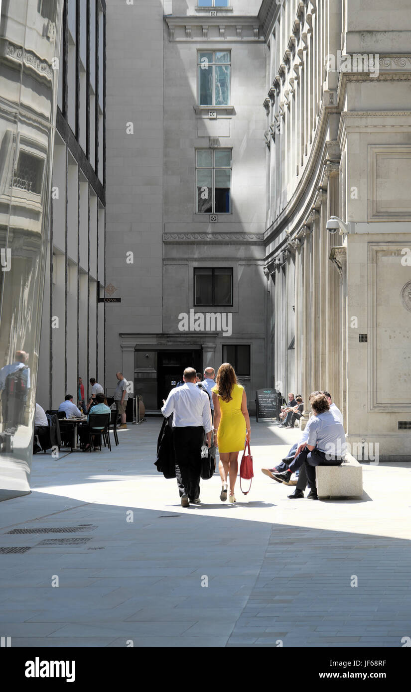Rear view of stylish businesswoman in yellow summer dress walking through courtyard in The City of London UK  KATHY - Stock Image