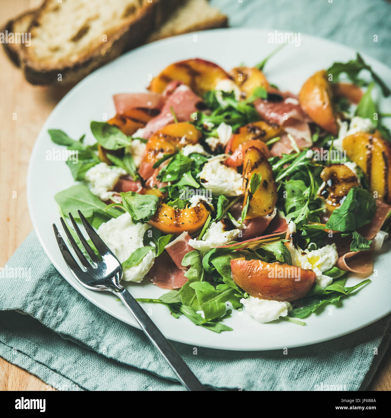 Arugula, prosciutto, mozzarella and grilled peach salad - Stock Image