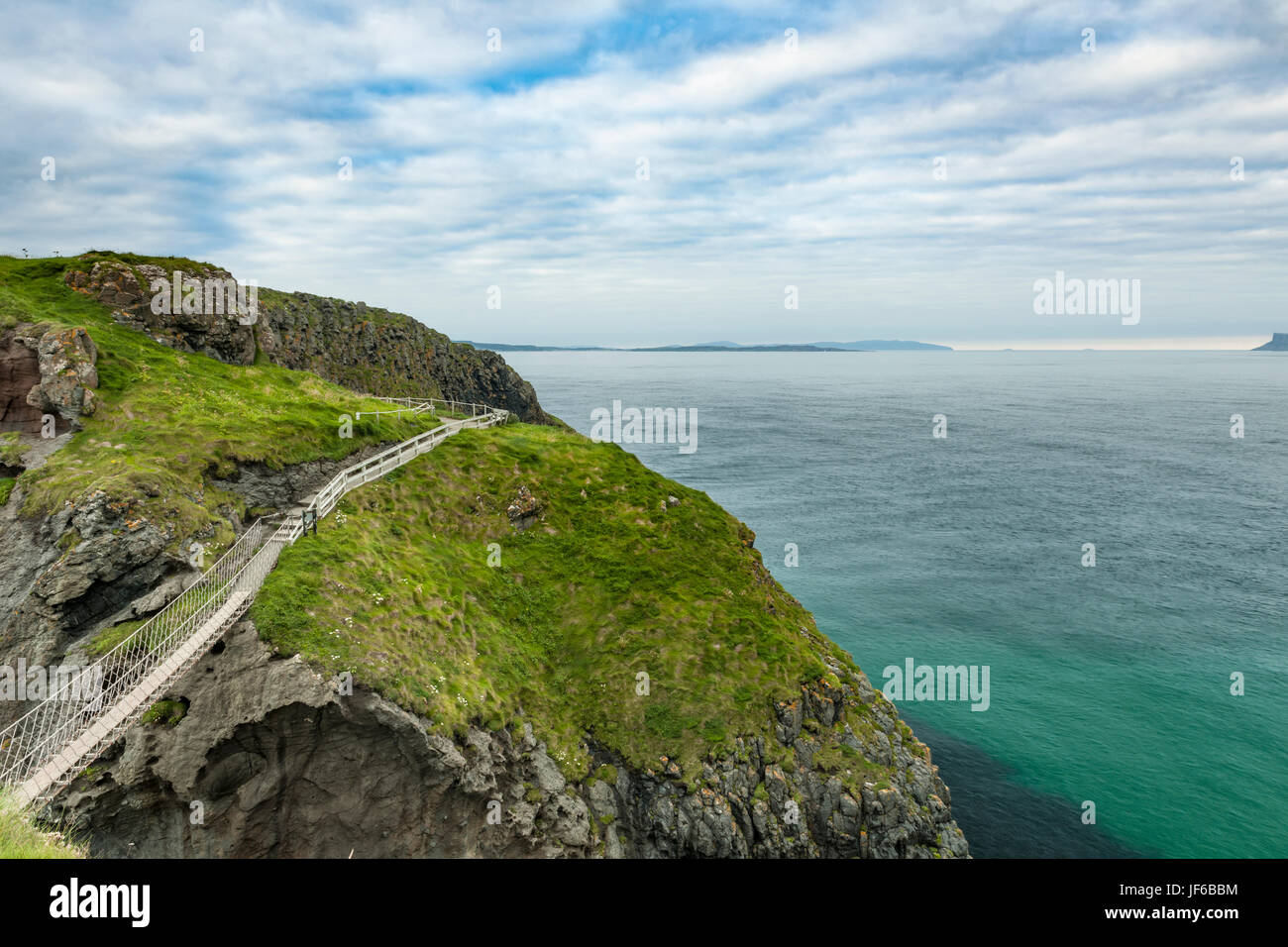 Scenic coastal view along pathway out to Carrick-a-rede rope bridge, Northern Ireland - Stock Image