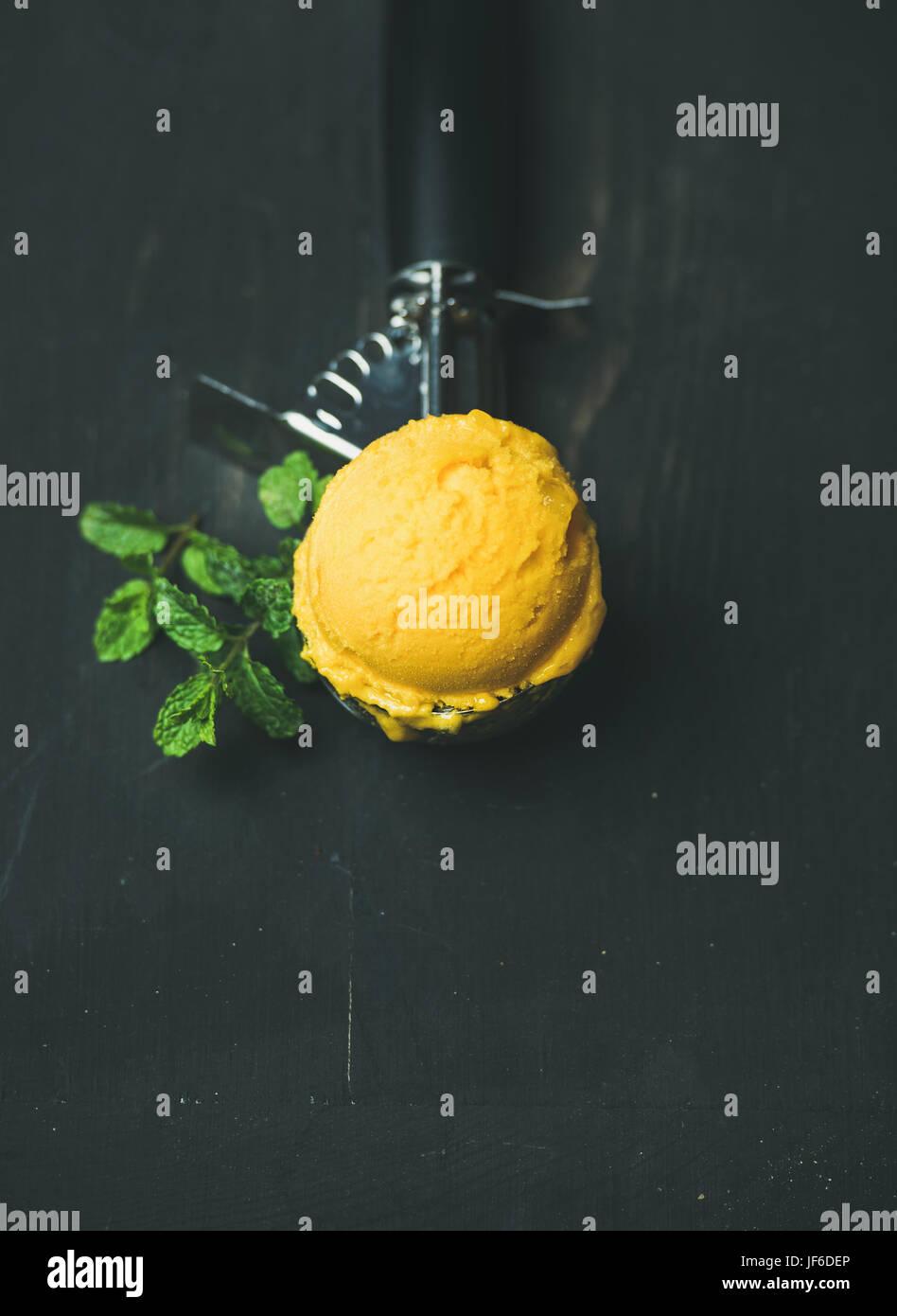 Mango sorbet ice cream scoop in ice cream scooper - Stock Image