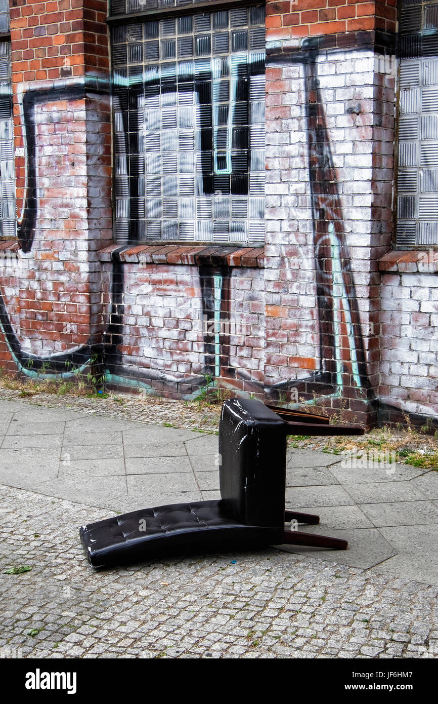 Urban decay, broken chair discarded,dumped,abandoned next to wall covered in graffiti tags - Stock Image