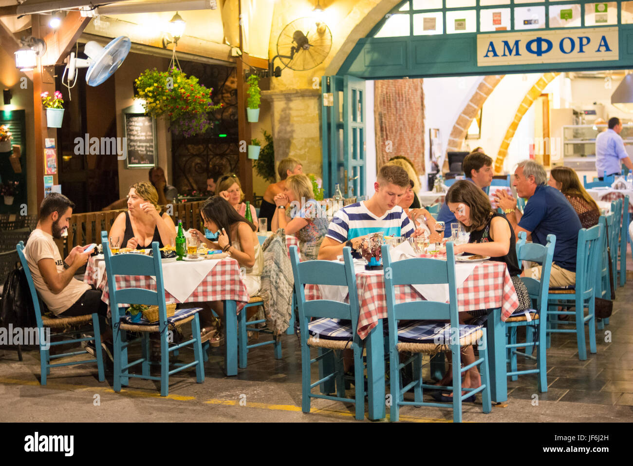 People eating in a  traditional restaurant on the waterfront of the town of Chania, Crete, Greek Islands, Greece - Stock Image