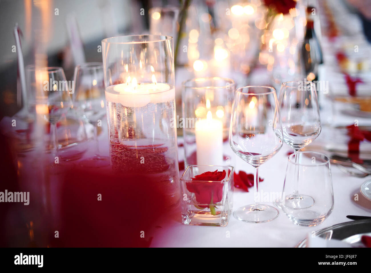 Romantic candlelit dinner table setting with elegant glassware and red flowers over a white tablecloth in a close - Stock Image