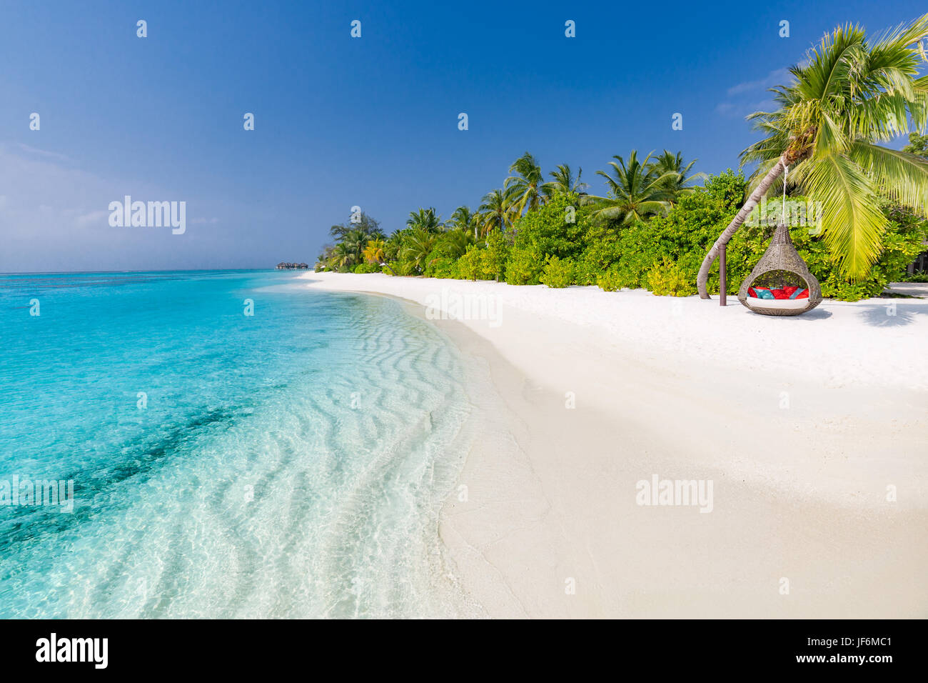 Perfect tropical beach. Romantic hammock or swing on white sand beach and palm trees under blue sky. Inspirational - Stock Image