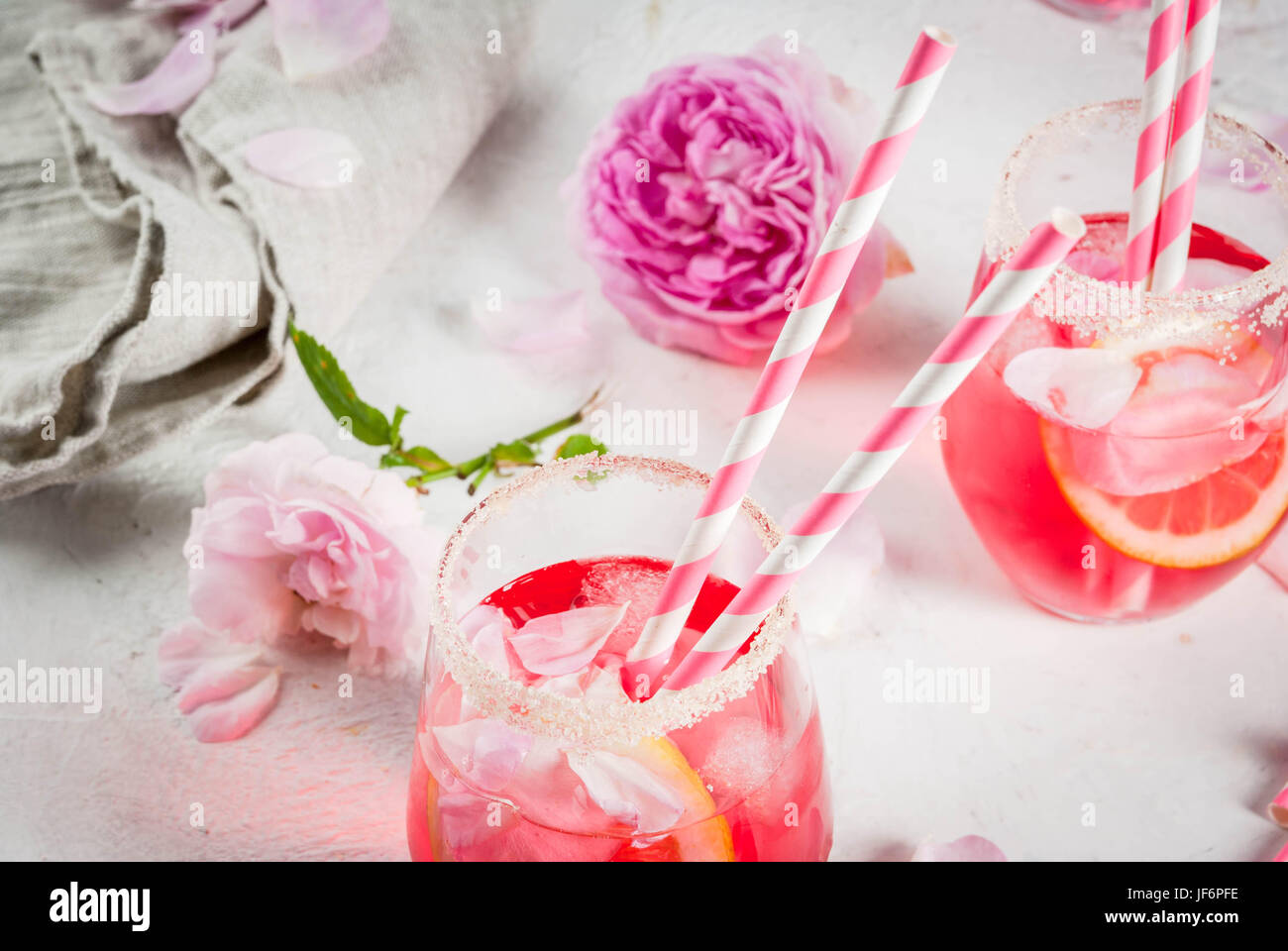 Summer refreshment drinks. Light pink rose cocktail, with rose wine, tea rose petals, lemon. On a white stone concrete table. With striped pink tubule Stock Photo