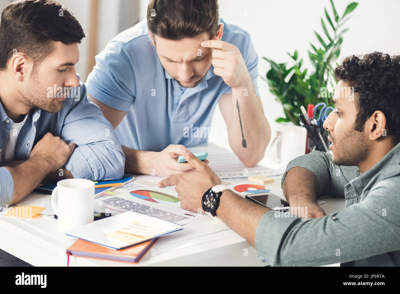 Three young businessmen sitting at table and working on new project together, business teamwork concept - Stock Image