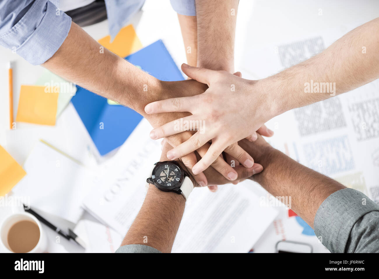 Close-up partial view of businessmen stacking hands while working on project together, business teamwork concept - Stock Image