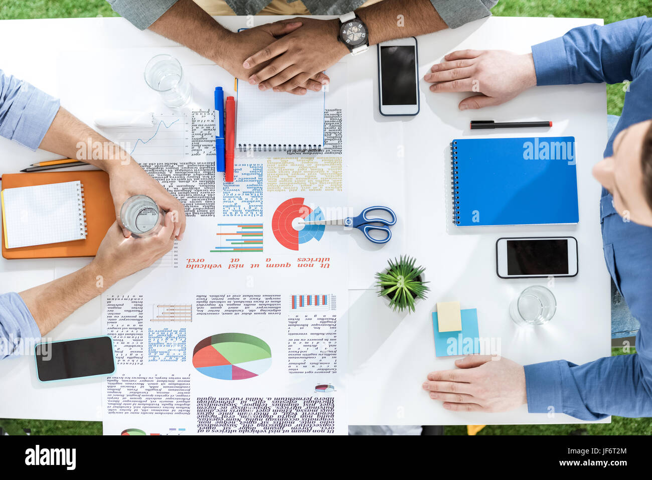 Overhead view of young businessmen sitting at table with papers and discussing new project, business teamwork concept - Stock Image