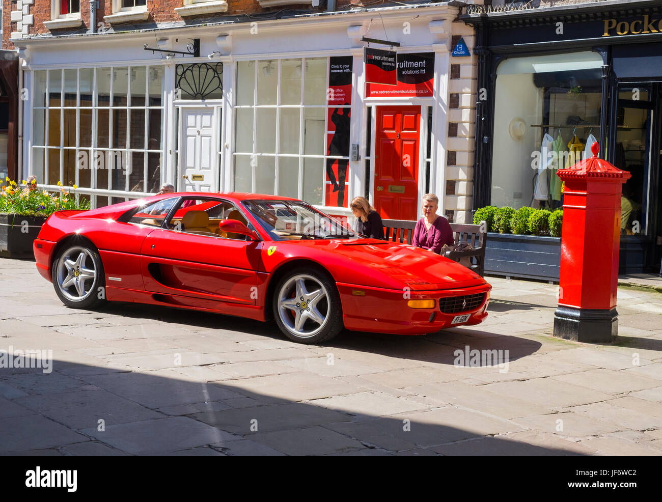 Red Ferrari sports car red door and red Penfold pillar box in The Square Shrewsbury Shropshire England UK & Red Ferrari sports car red door and red Penfold pillar box in The ...