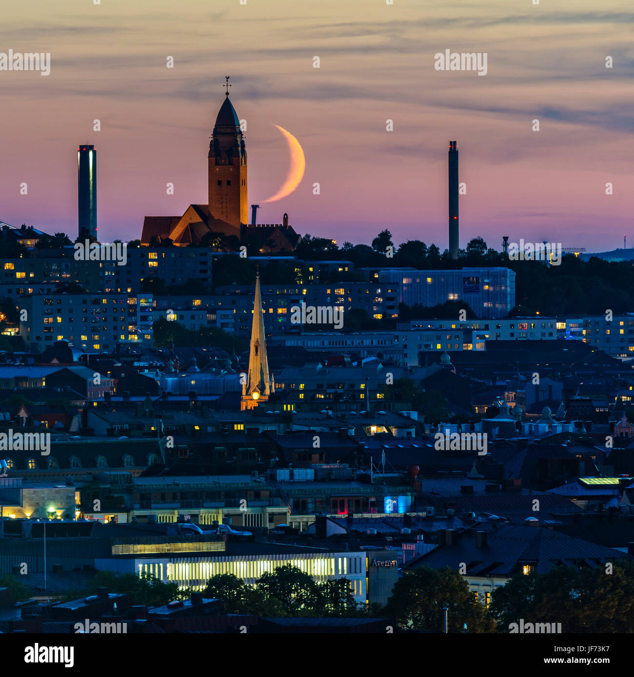 Crescent moon above city at dusk - Stock Image