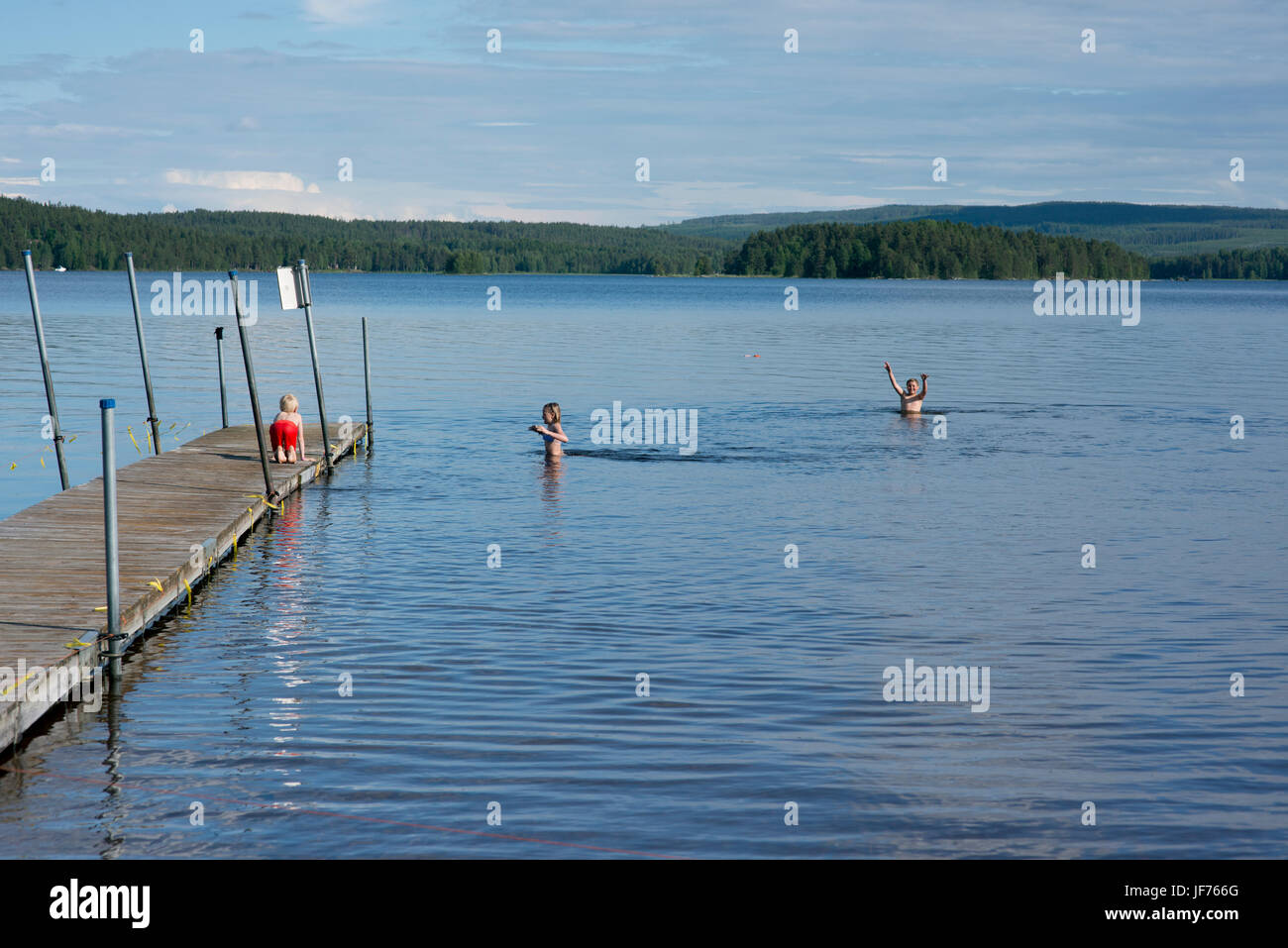Three boys swimming in lake - Stock Image