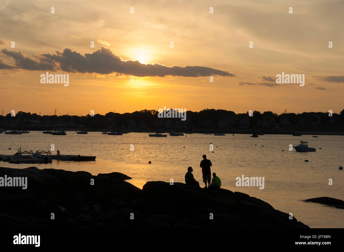 Group of friends enjoying each other's company on the shore of Beverly Harbor, at sunset. Salem Willows Park, - Stock Image