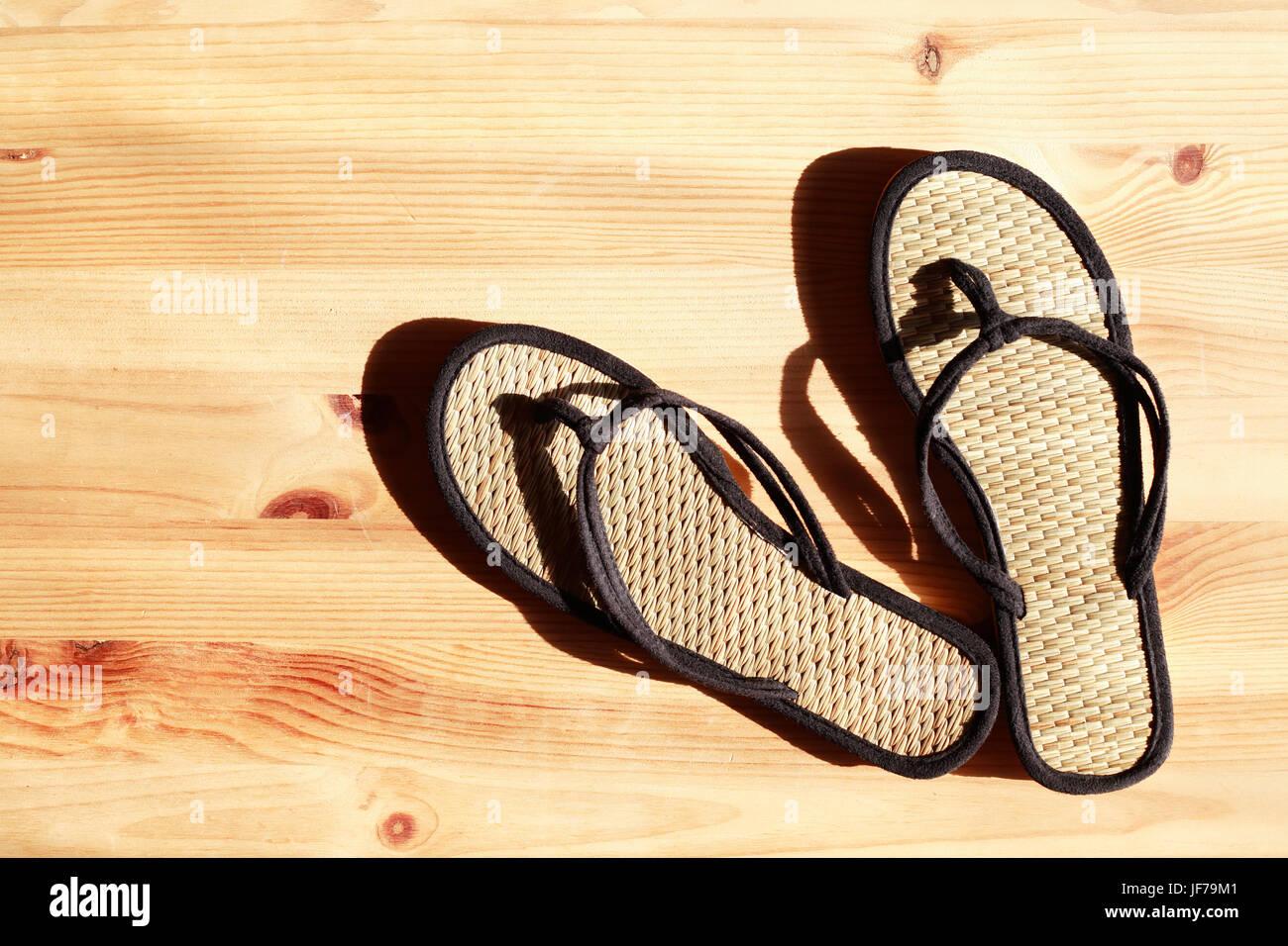 b57032c4f37 Pair of female flip-flops on wooden floor under sunbeam - Stock Image