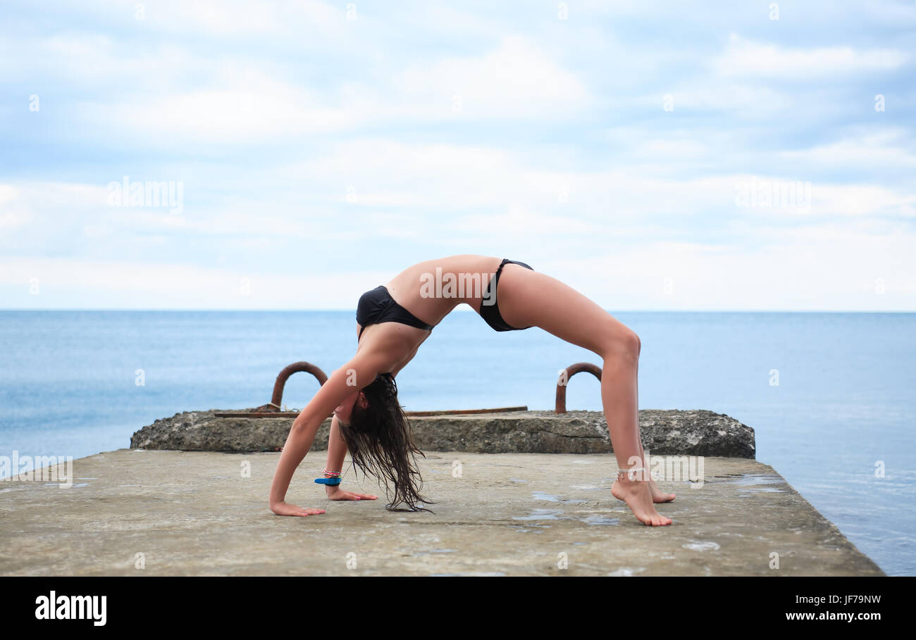 Young beauty teenage girl doing exercise on pier near sea Stock Photo
