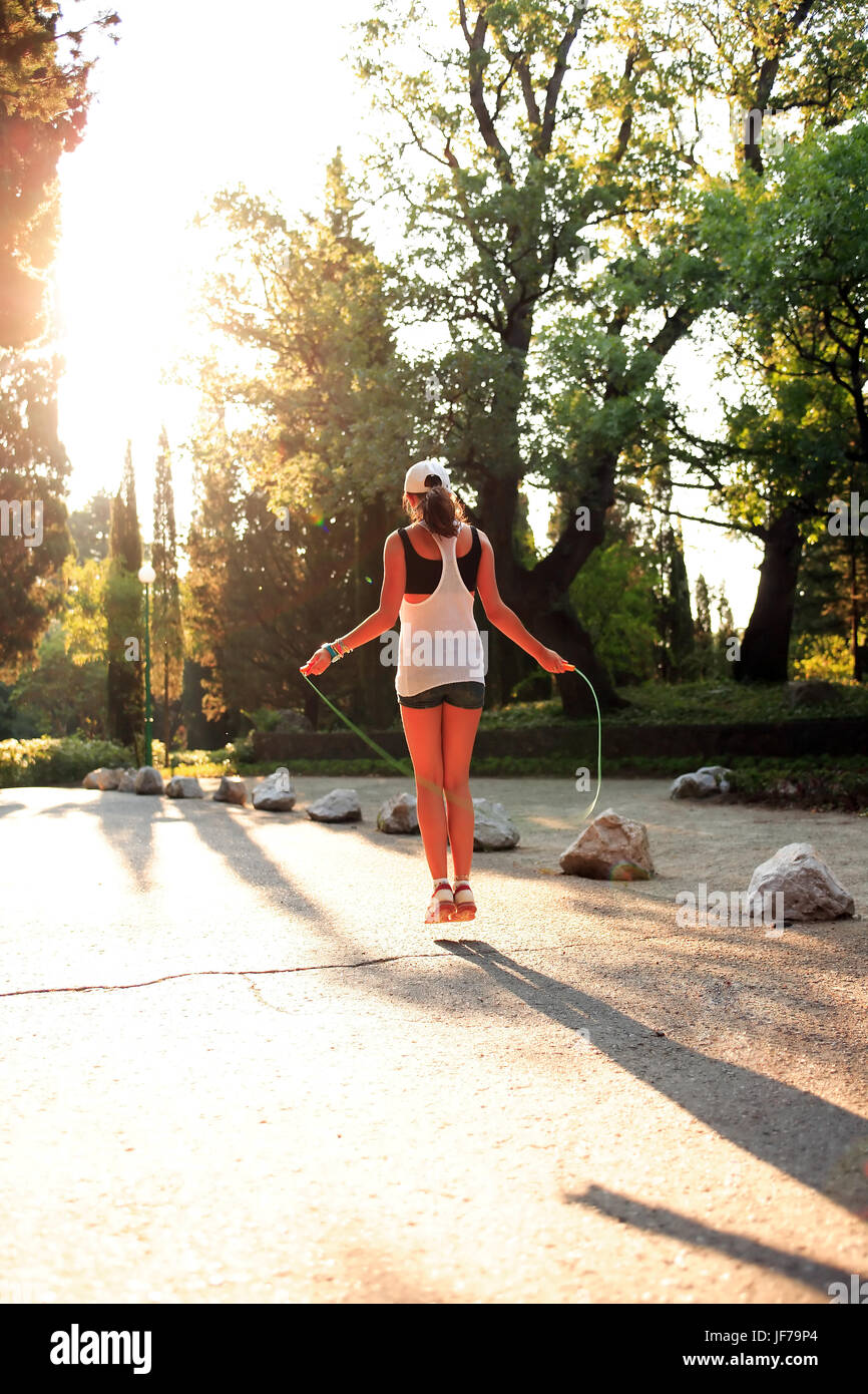 Beauty svelte teenage girl jumping rope in morning park - Stock Image