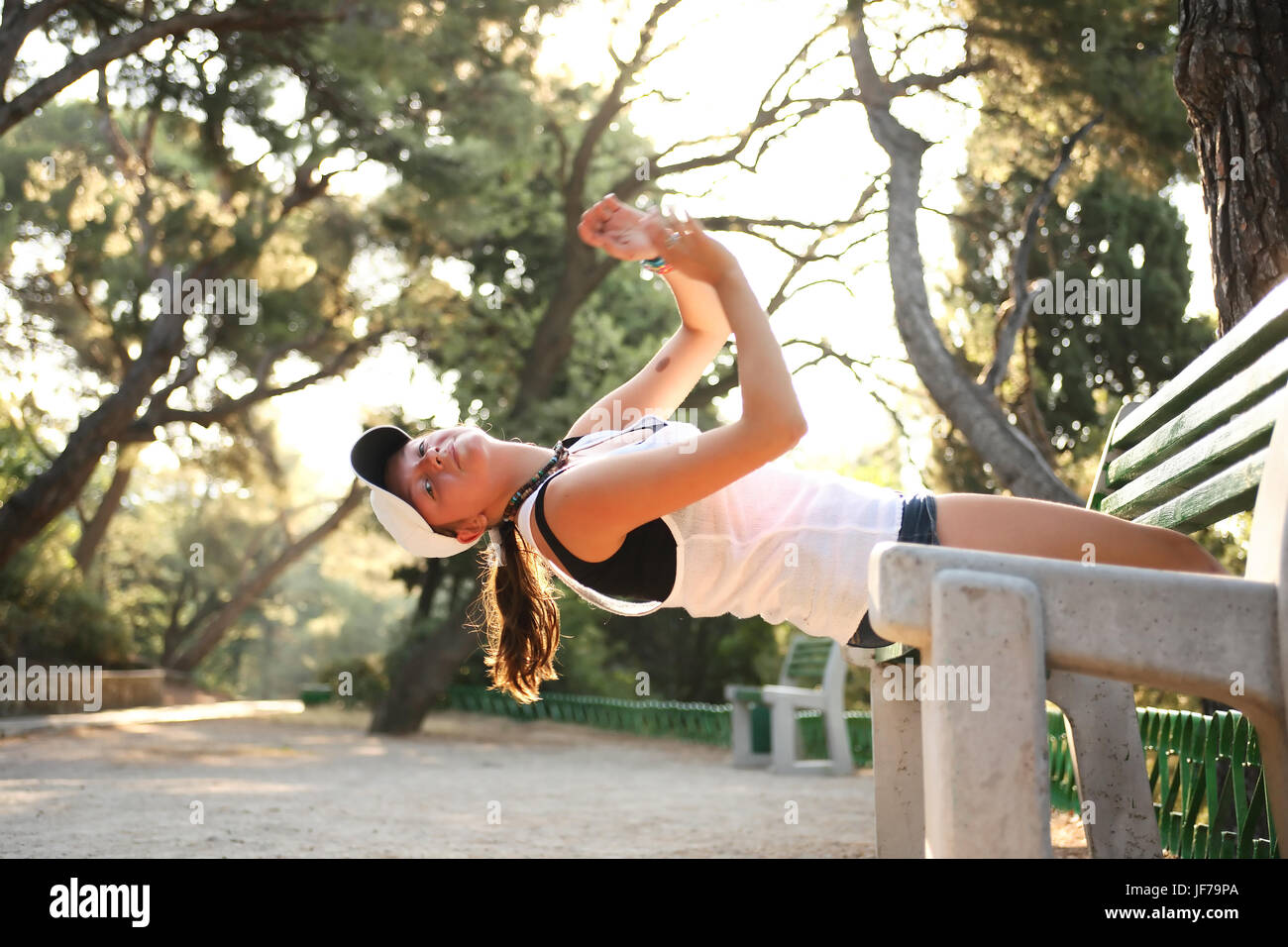 Beauty teenage girl doing exercise on bench in morning park Stock Photo