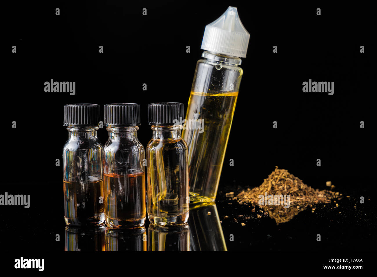 E-liquid bottles next to grinded tobacco leaves and smoke cloud - Stock Image