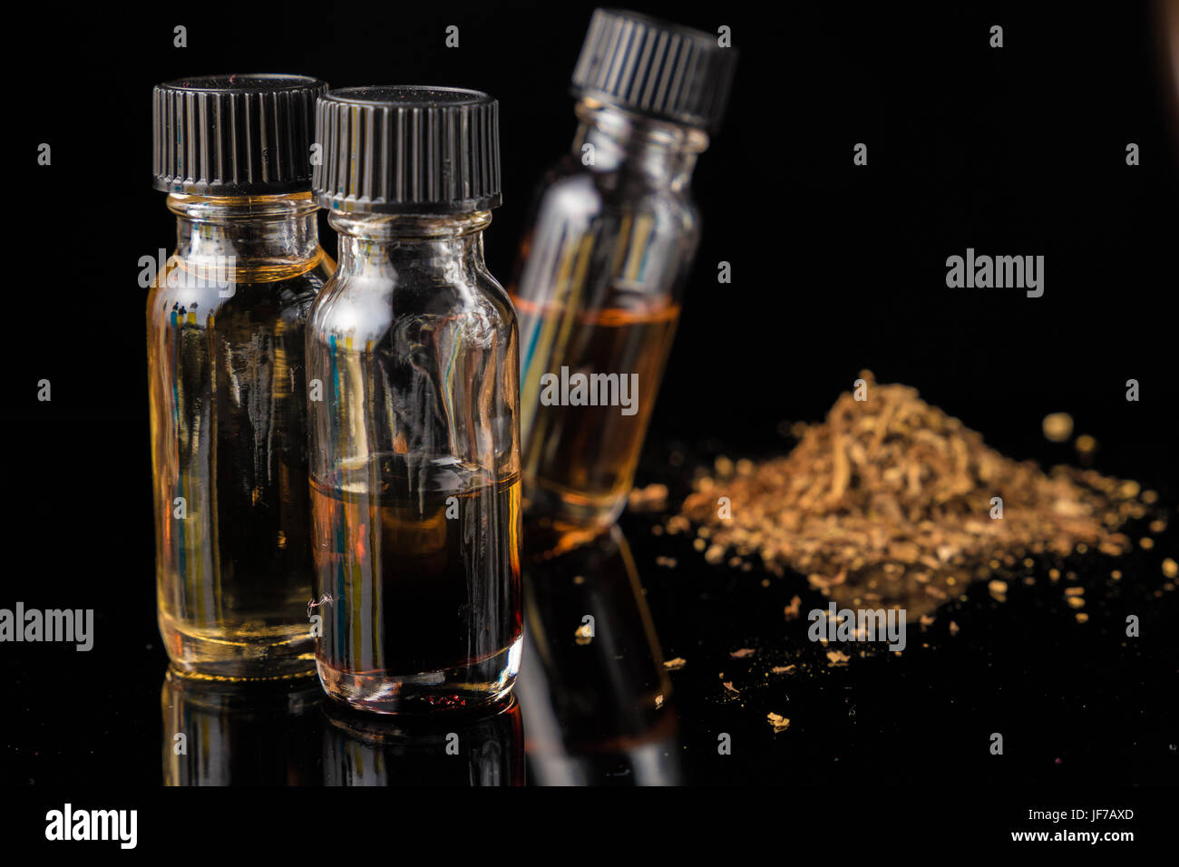 E-liquid bottles next to grinded tobacco leaves - Stock Image