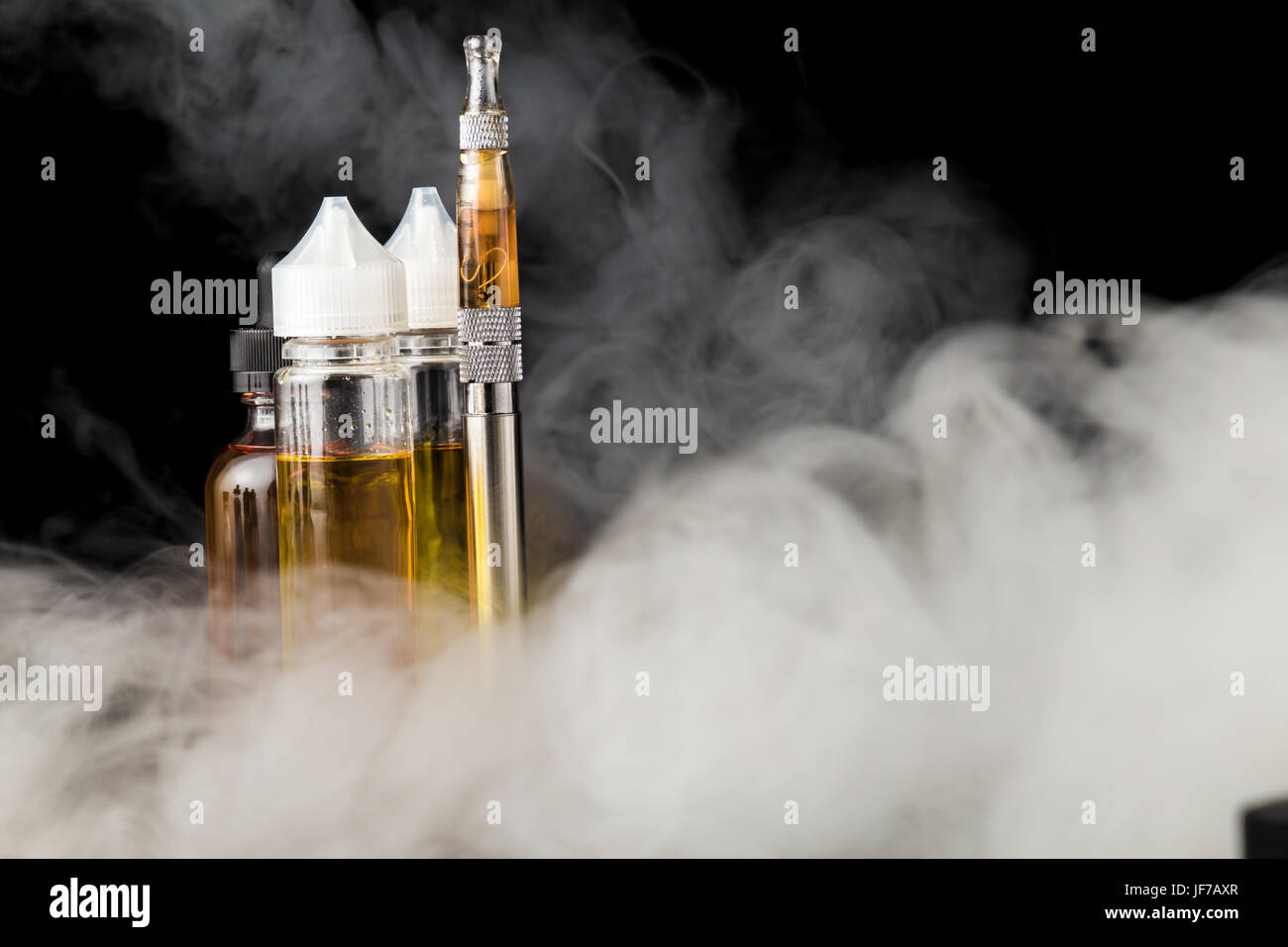 Electronic cigarette with bottles and big cloud of smoke Stock Photo