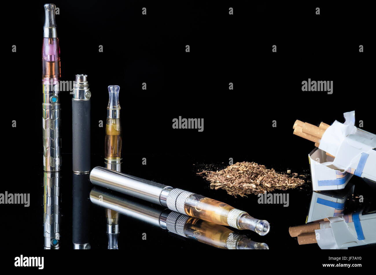 E-cigarette with pile of grinded tobacco leaves and a pack of smokes [FIX] - Stock Image