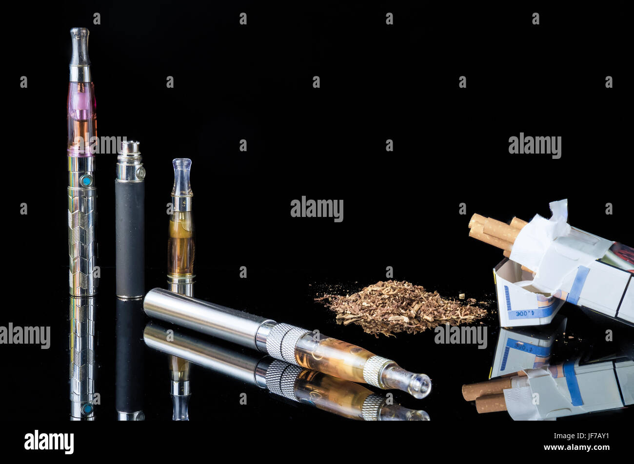 E-cigarette with pile of grinded tobacco leaves and a pack of smokes - Stock Image