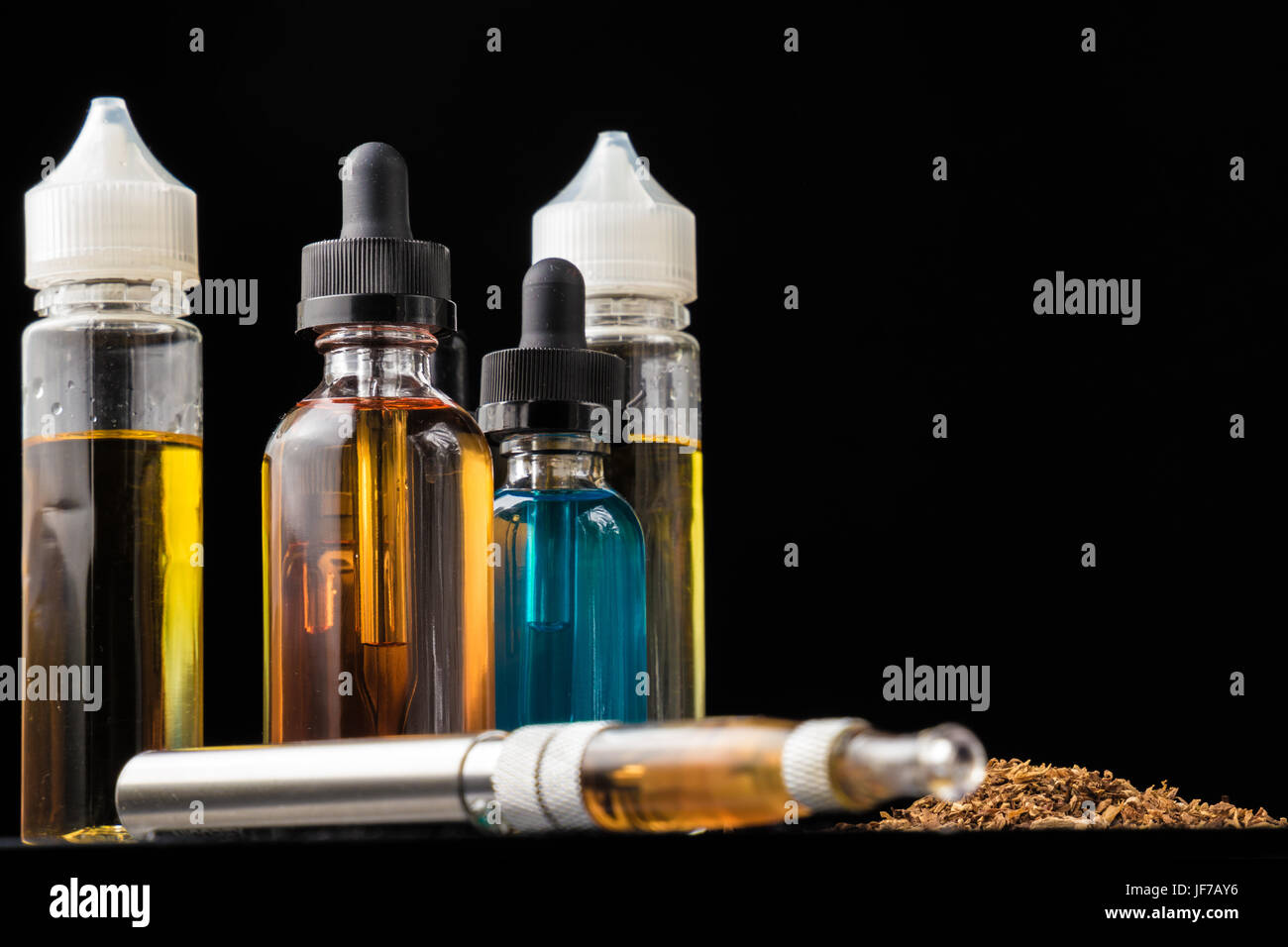 E-liquid bottles and e-cigarette with pile of grinded tobacco leaves - Stock Image