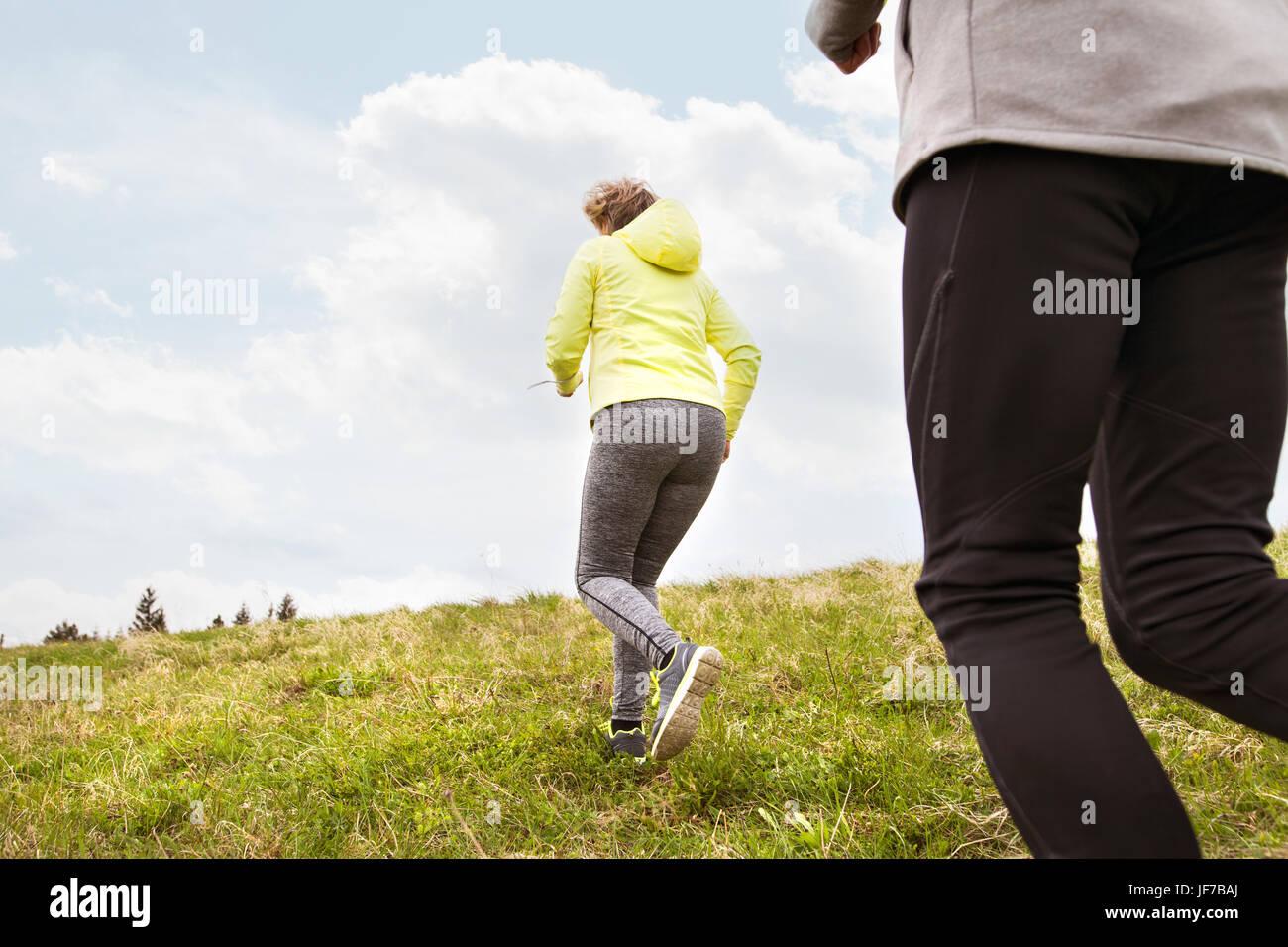 Unrecognizable senior couple running outside on green hills. - Stock Image