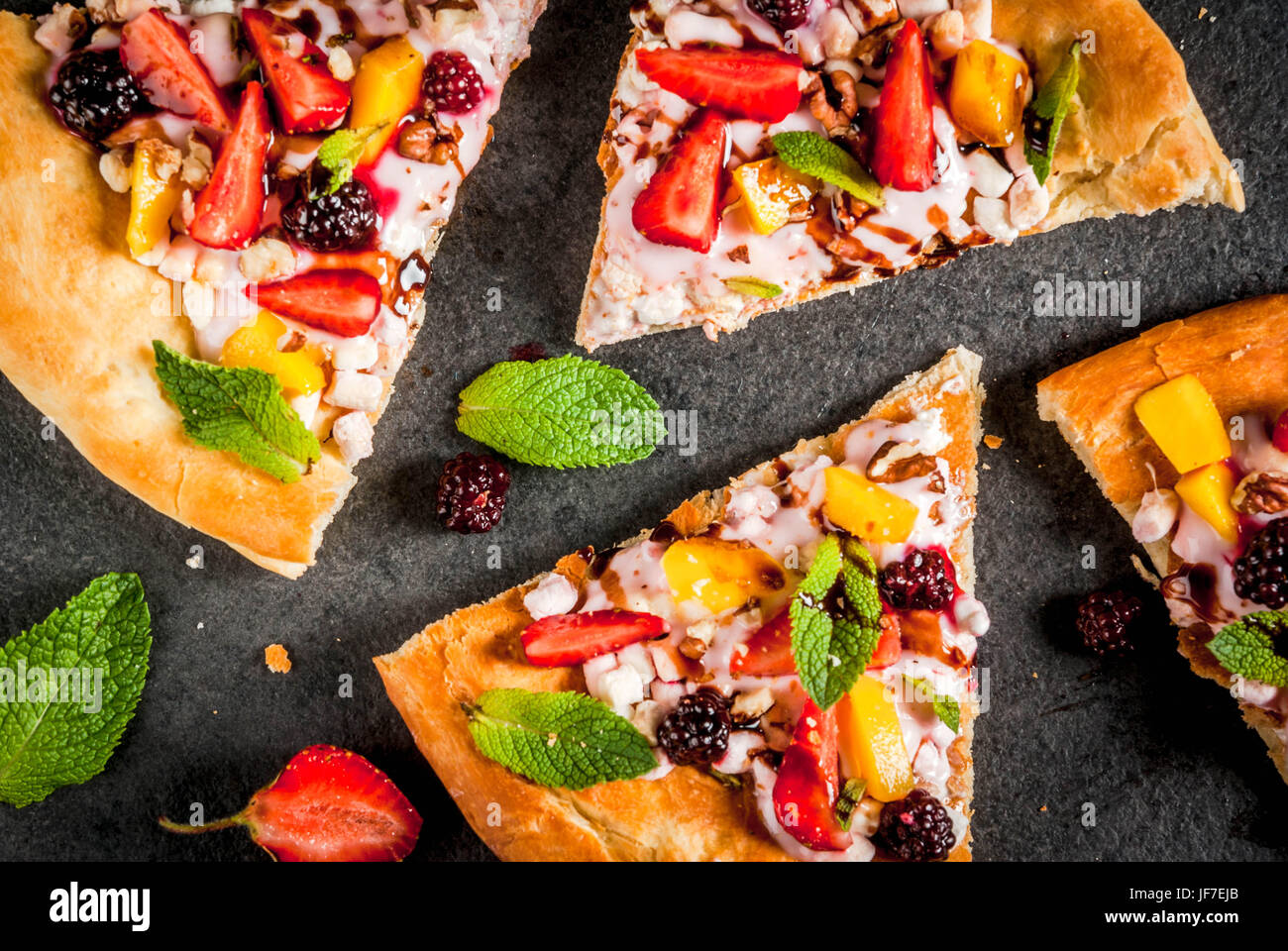 Summer snacks. Food for party. Fruit pizza with cream, currants, yogurt, strawberries, mango, peaches, bananas, - Stock Image
