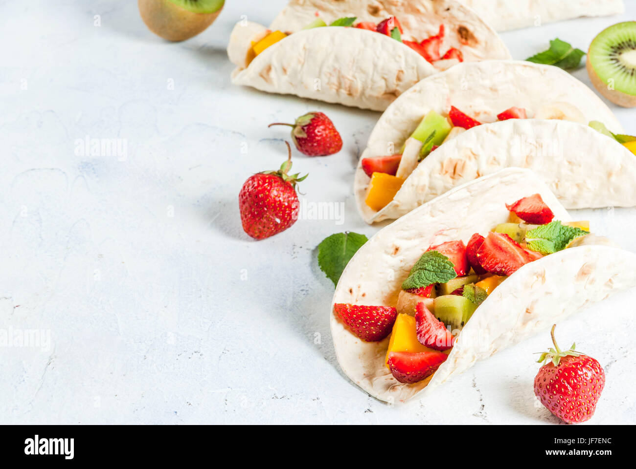 Summer snacks. Food for a party. Fruit tacos with strawberries, mangoes, bananas, chocolate, mint. On a light blue - Stock Image