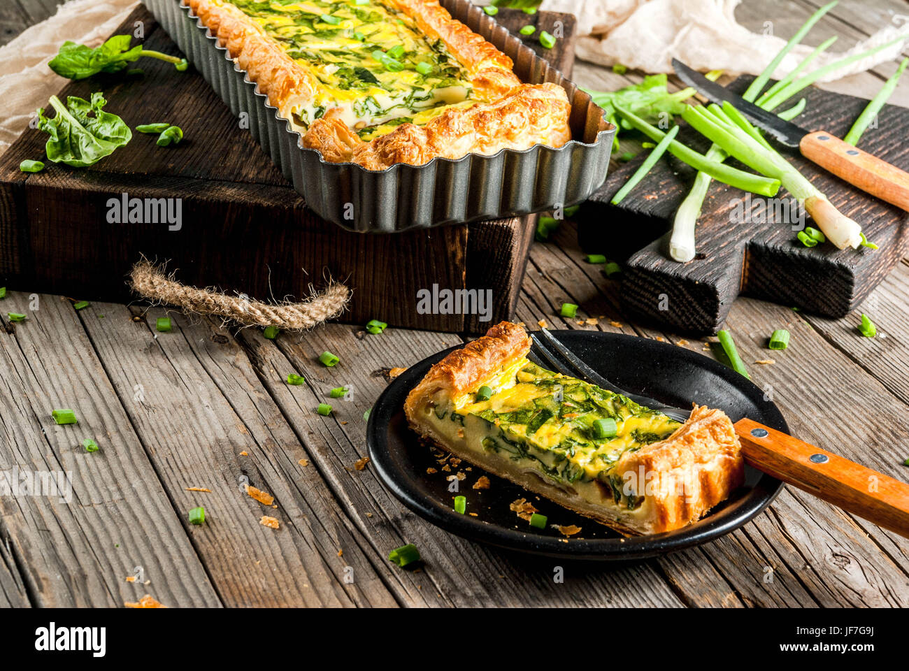 French home cooking. Casserole. Pie. quiche lorraine from puff pastry, with young green onions and spinach. On old - Stock Image