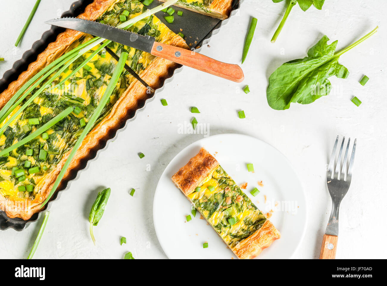 French home cooking. Casserole. Pie. quiche lorraine from puff pastry, with young green onions and spinach. On white - Stock Image