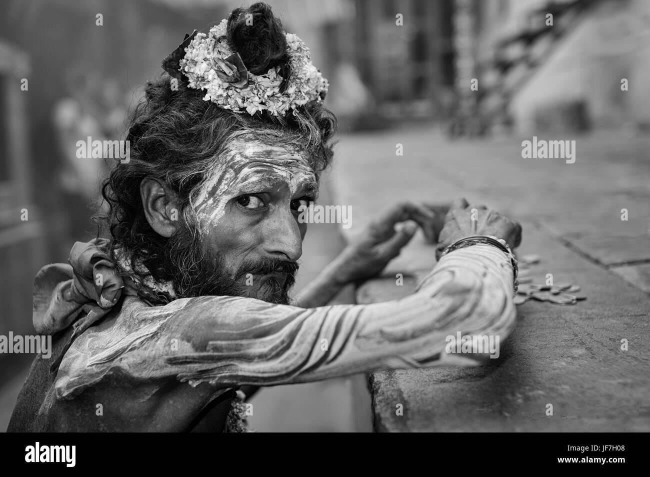 Sadhu, Hindu religious man, with face paint and flowers, counts his meager takings from begging in Varanasi, Uttar - Stock Image