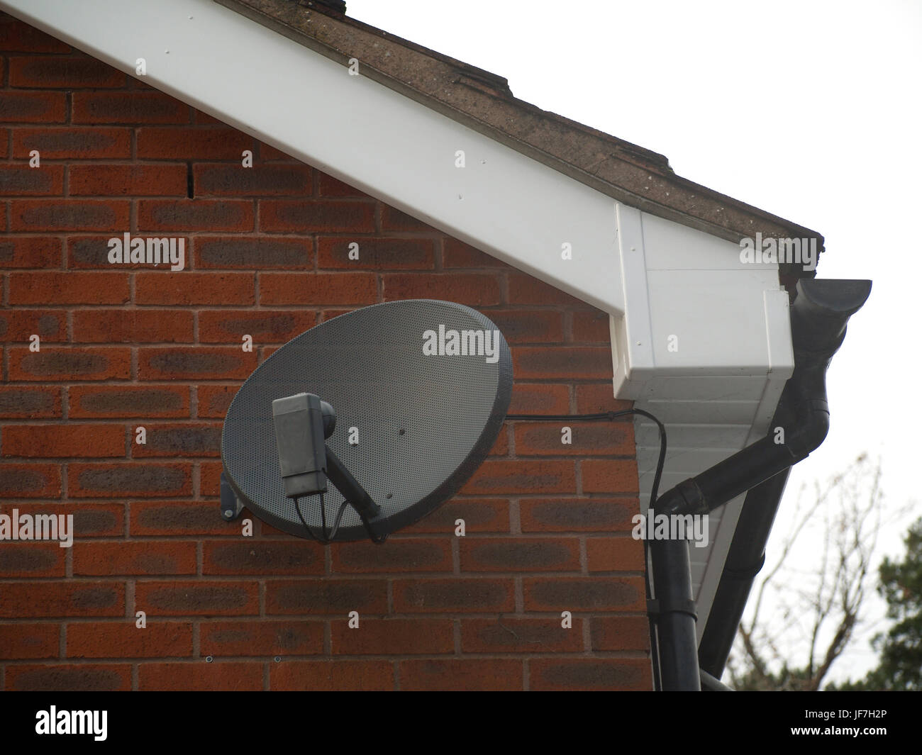 Sky dish mounted on traditional red brick British house - Stock Image
