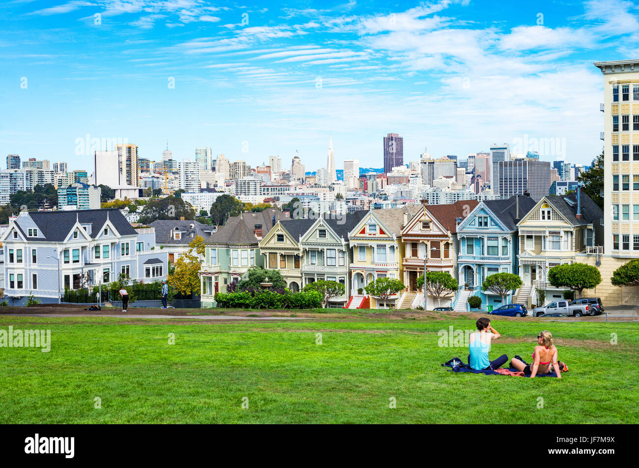 San Francisco, USA,  The colored traditional houses of Alamo square with the cityscape on background - Stock Image