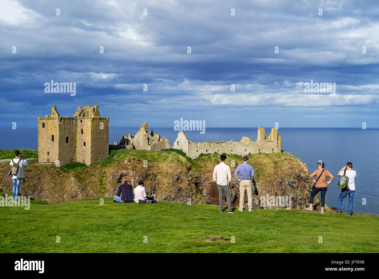 Tourists looking at Dunnottar Castle, ruined medieval fortress near Stonehaven on cliff along the North Sea coast, - Stock Image