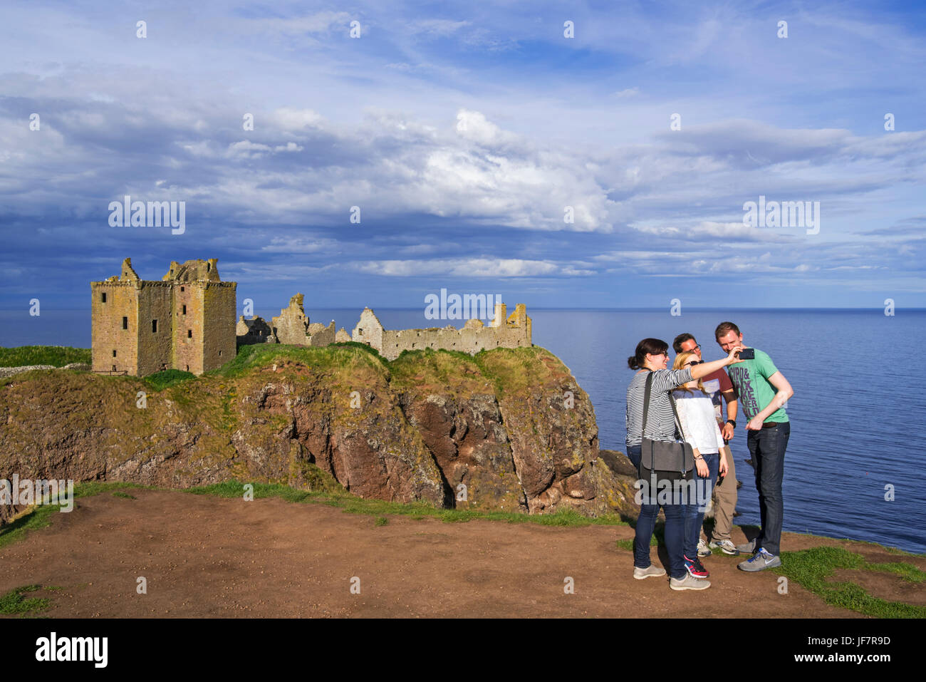 Tourists taking selfies at Dunnottar Castle, ruined medieval fortress near Stonehaven on cliff along the North Sea - Stock Image