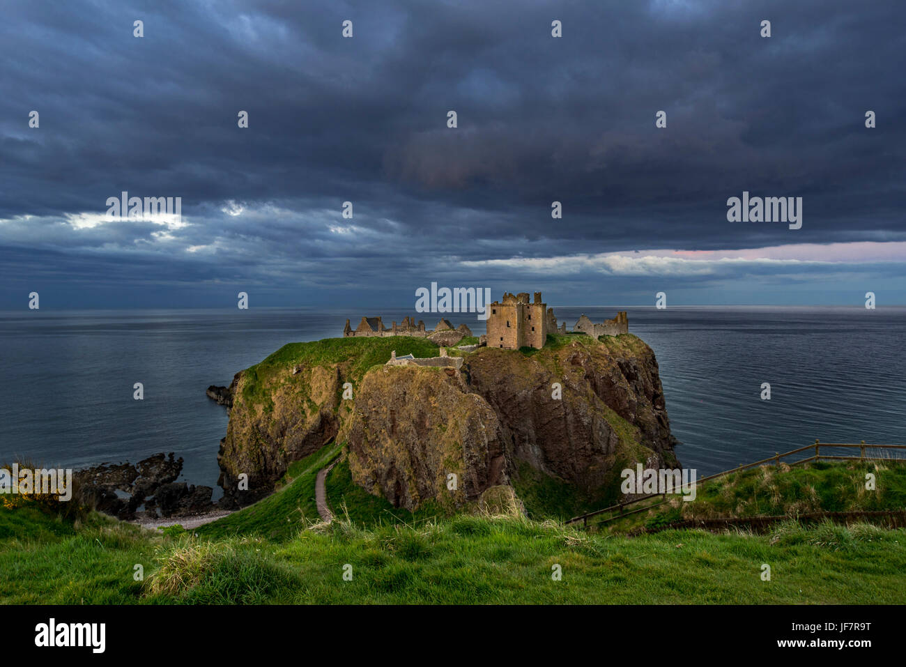 Menacing dark clouds above Dunnottar Castle, ruined medieval fortress near Stonehaven on cliff along the North Sea - Stock Image
